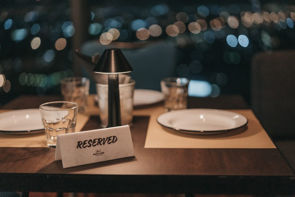A 'reserved' sign is on a table laid with plates and glasses. A small table lamp provides some light, there are small dots of light shining in the background.